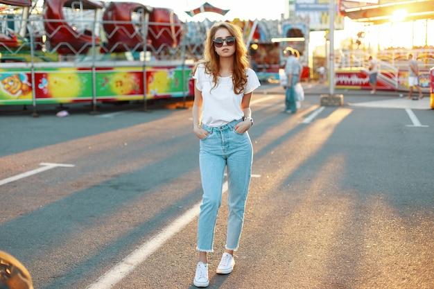 Redhead carino giovane donna hipster in elegante t-shirt in occhiali da sole alla moda in blue jeans pone in un parco di divertimenti