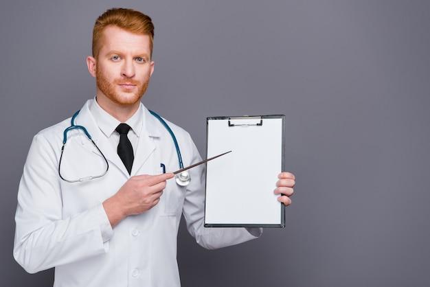 Redhead medico con camice da laboratorio in posa contro il muro grigio