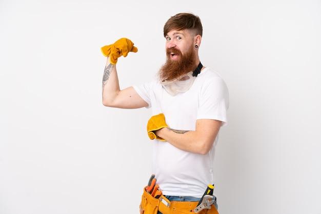 Uomo dell'elettricista di redhead con la barba lunga sopra la parete bianca che fa gesto forte