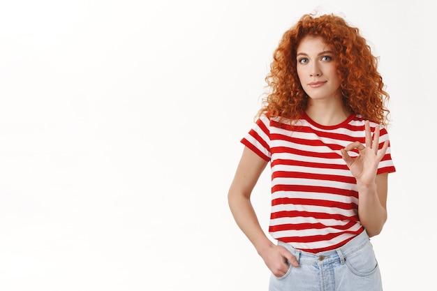 La ragazza dai capelli rossi approva il check out buona scelta mostra ok ok segno sorridente contento tenere tasca mano posa sicura, stilista d'accordo vestito scelto come buona idea, in piedi muro bianco