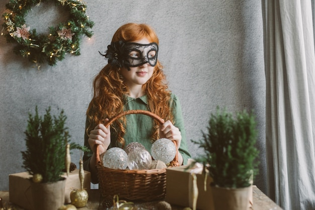 Ragazza rossa in una maschera di carnevale tiene un cesto con decorazioni natalizie.