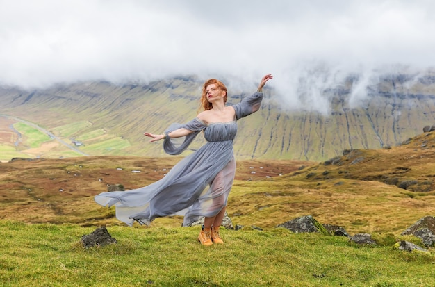 Una ragazza dai capelli rossi in abiti alla moda che balla tra le nuvole. isole faroe