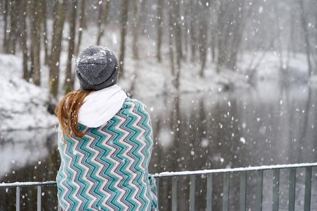 Ragazza rossa in cappello grigio, ricoperta di plaid blu modelli godendo nevicata in piedi sul retro sul ponte vicino al fiume e guardando il fiume