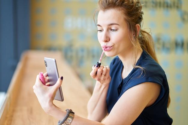 Ragazza rossa che mette il rossetto da sola, guardando alla riflessione su smartphone