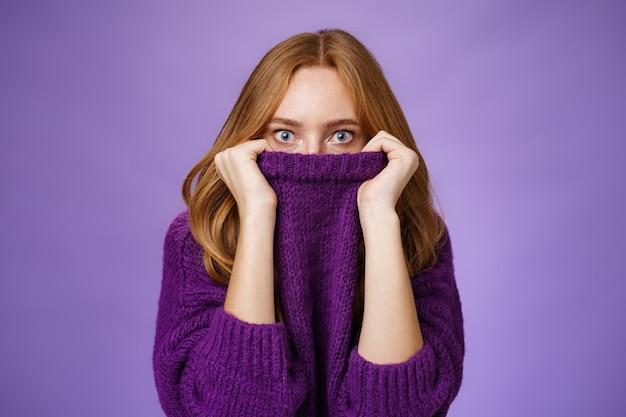 La ragazza rossa spaventata dall'inverno sta arrivando nascondendosi nel colletto di un maglione caldo che fa schioccare gli occhi scioccata e stordita alla telecamera come se fosse spaventata e insicura in piedi terrorizzata su sfondo viola.