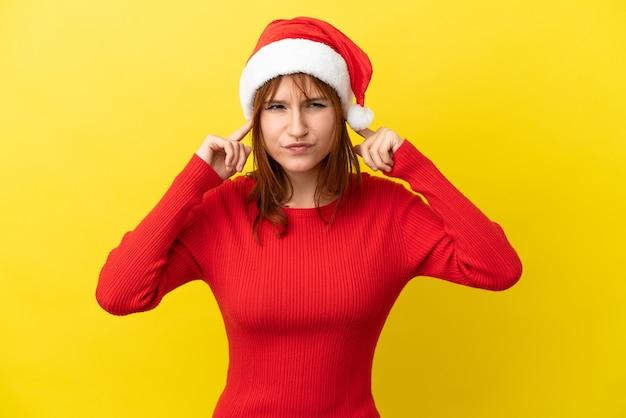 Ragazza rossa con cappello di natale isolato su sfondo giallo frustrata e che copre le orecchie