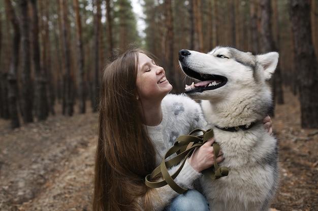 Ragazza rossa con le lentiggini con il suo cane husky nella foresta di autunno