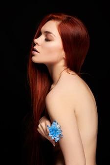 Ragazza rossa con il ritratto di arte di contrasto di capelli lunghi. donna perfetta su sfondo nero. capelli stupendi e occhi stupendi. bellezza naturale, pelle pulita, cura del viso e dei capelli. capelli forti e folti