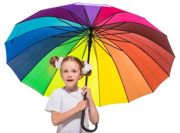 Ragazza della testarossa con l'ombrello di colore dell'arcobaleno nelle mani su una superficie bianca isolata
