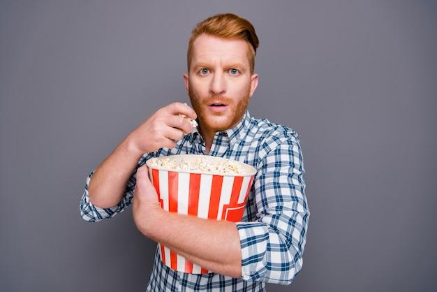 Ragazzo dai capelli rossi in una camicia a scacchi blu in posa contro il muro grigio