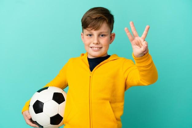 Ragazzo dai capelli rossi che gioca a calcio isolato su sfondo blu felice e conta tre con le dita