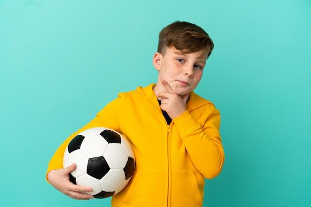 Ragazzo dai capelli rossi che gioca a calcio isolato su sfondo blu avendo dubbi