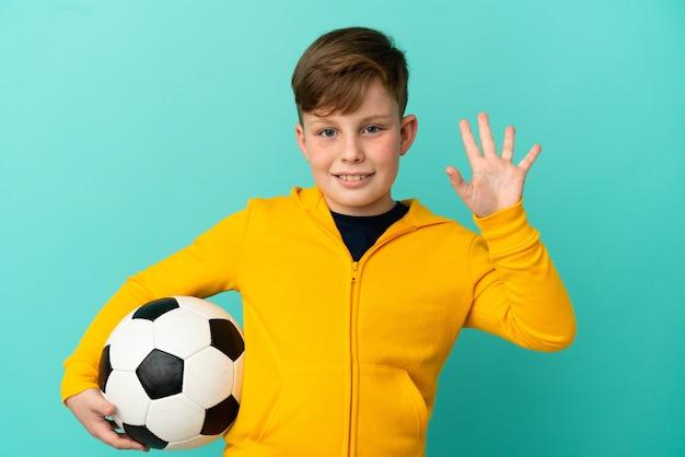 Bambino dai capelli rossi che gioca a calcio isolato su sfondo blu salutando con la mano con espressione felice