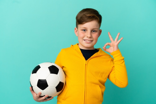 Ragazzo dai capelli rossi che gioca a calcio isolato su sfondo blu che mostra segno ok con le dita