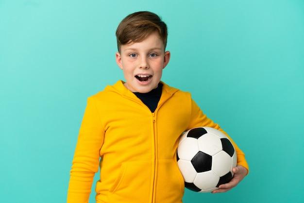 Ragazzo dai capelli rossi che gioca a calcio isolato su sfondo blu con espressione facciale a sorpresa
