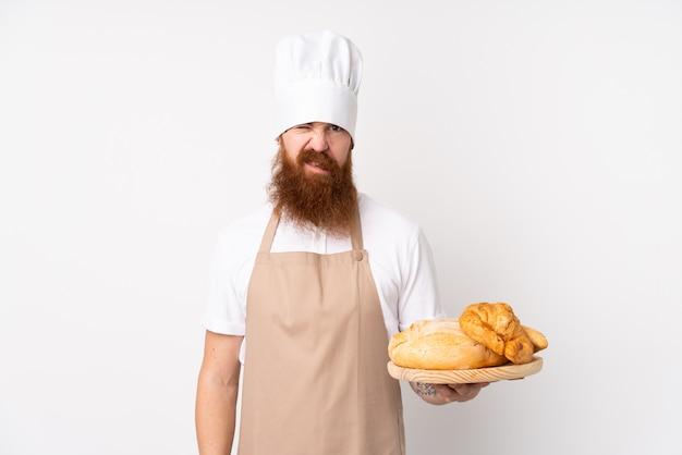 Redhead in uniforme da chef. panettiere maschio che tiene una tabella con parecchi pani con l'espressione triste