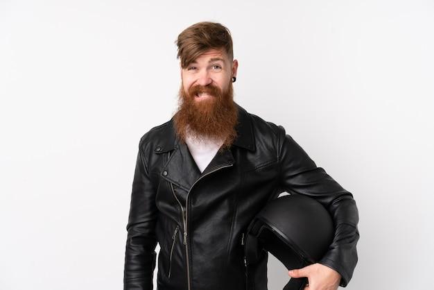 Uomo di redhead con la barba lunga che tiene un casco del motociclo sopra la parete bianca isolata che ha dubbi e con l'espressione confusa del fronte