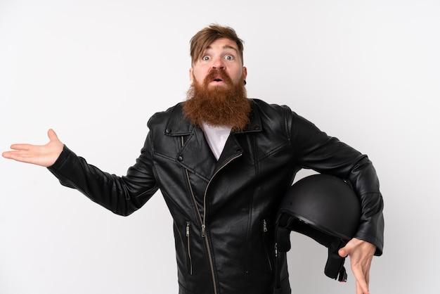 Uomo di redhead con la barba lunga che tiene un casco del motociclo sopra la parete bianca isolata che ha dubbi con l'espressione confusa del fronte