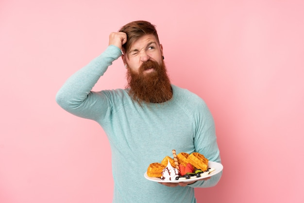 L'uomo di redhead con la barba lunga che tiene i waffles sopra la parete rosa isolata che ha dubbi e con l'espressione confusa del fronte