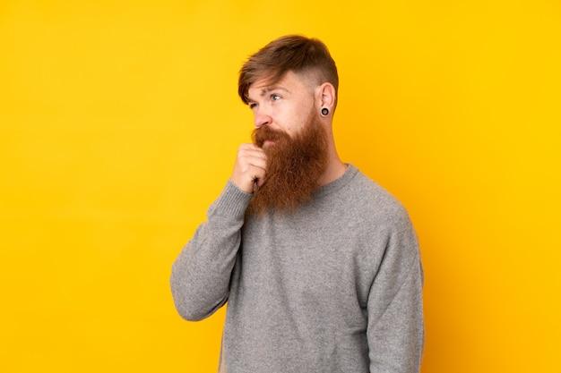 Redhead uomo con la barba lunga sul muro giallo isolato con dubbi e con espressione faccia confusa
