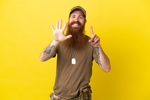 Redhead militare con dog tag isolato su sfondo giallo contando sei con le dita