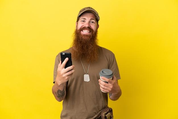 Redhead militare con dog tag isolato su sfondo giallo tenendo il caffè da portare via e un mobile