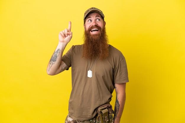 Redhead militare con dog tag isolato su sfondo giallo con l'intenzione di realizzare la soluzione mentre si solleva un dito