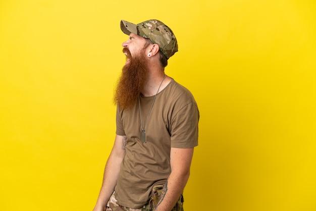 Redhead militare con dog tag isolato su sfondo giallo ridendo in posizione laterale