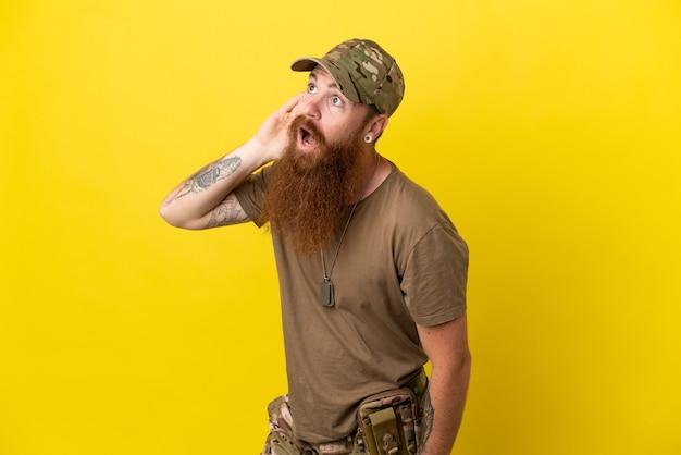 Redhead militare con dog tag isolato su sfondo giallo ascoltando qualcosa mettendo la mano sull'orecchio