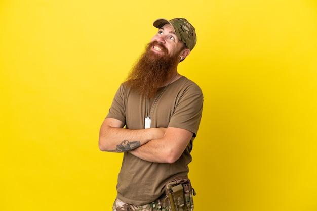 Redhead militare con dog tag isolato su sfondo giallo guardando in alto mentre sorridente