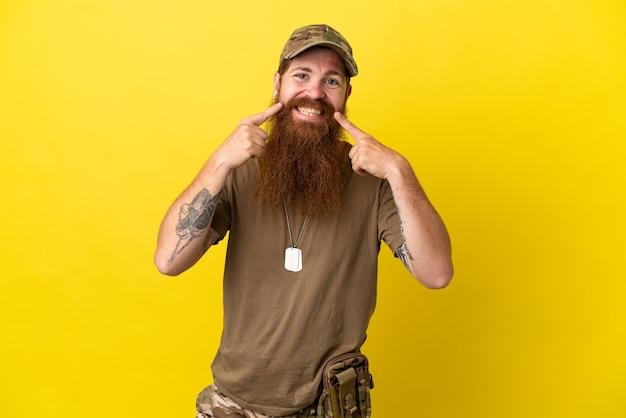 Redhead militare con dog tag isolato su sfondo giallo sorridente con un'espressione felice e piacevole