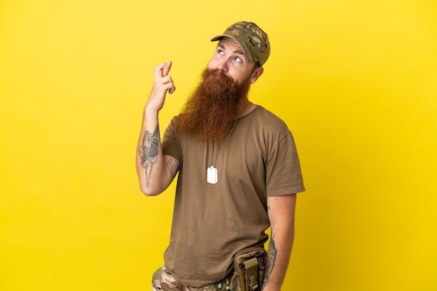 Redhead militare con dog tag isolato su sfondo giallo con le dita incrociate e augurando il meglio