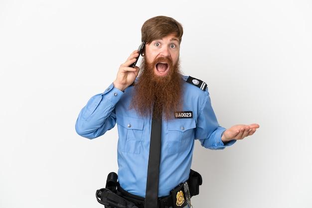 Uomo di polizia dai capelli rossi isolato su sfondo bianco che tiene una conversazione con il telefono cellulare con qualcuno