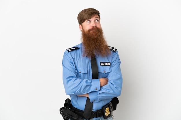 Uomo di polizia dai capelli rossi isolato su sfondo bianco che fa gesti di dubbi mentre solleva le spalle