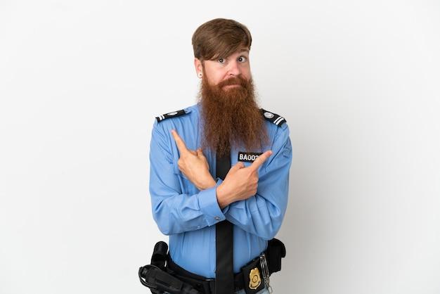 Redhead uomo di polizia isolato su sfondo bianco che punta ai laterali che hanno dubbi