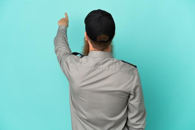 Uomo di sicurezza dai capelli rossi isolato su sfondo bianco che punta indietro con il dito indice