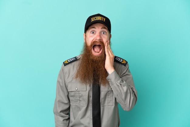 Uomo di sicurezza dai capelli rossi isolato su sfondo bianco con espressione facciale sorpresa e scioccata