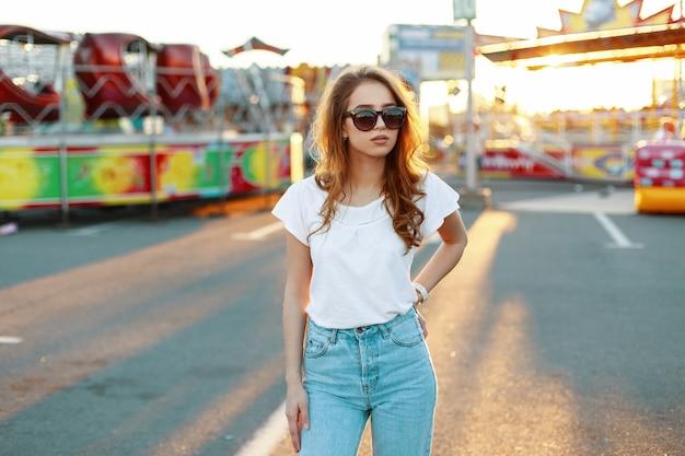 Redhead elegante giovane donna hipster in bianco alla moda in jeans vintage in occhiali da sole alla moda in un parco di divertimenti