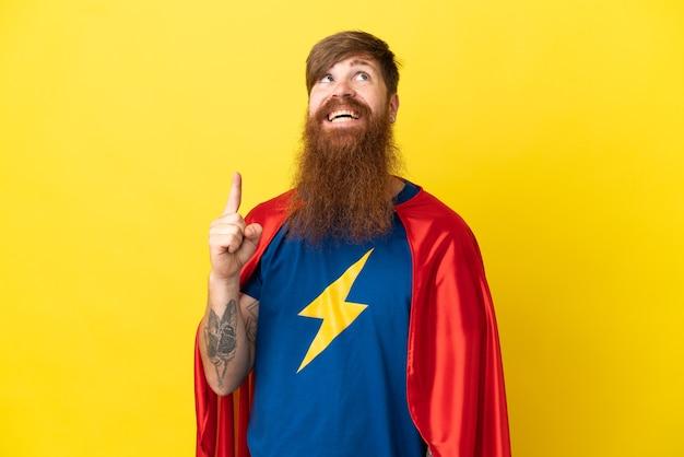 Redhead super hero uomo isolato su sfondo giallo rivolto verso l'alto e sorpreso