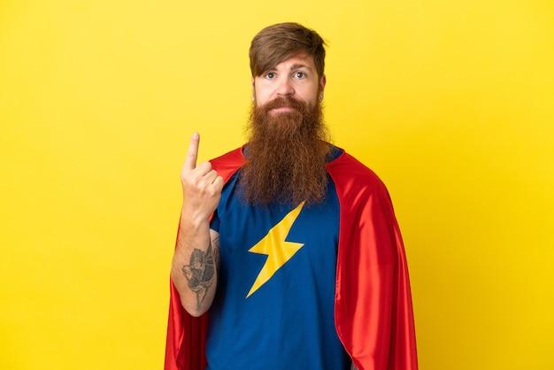 Redhead super hero uomo isolato su sfondo giallo che punta con il dito indice una grande idea