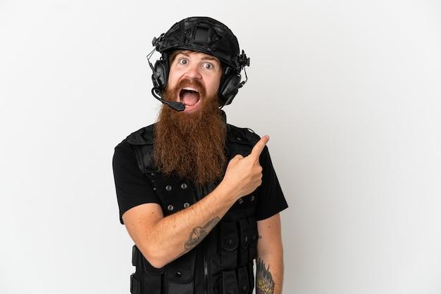 Redhead swat isolato su sfondo bianco sorpreso e indicando il lato