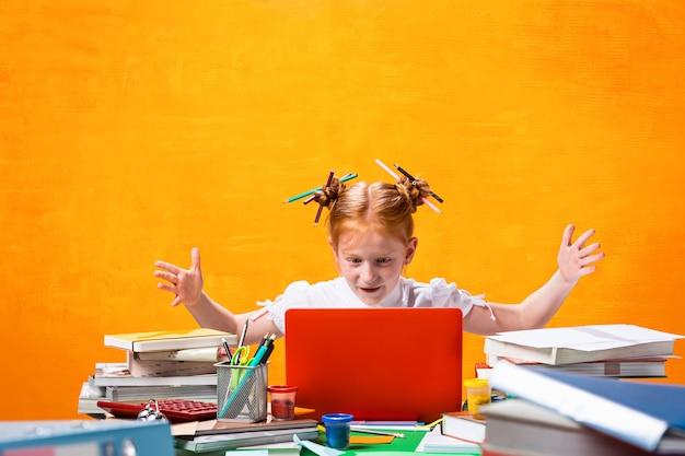 La ragazza adolescente dai capelli rossi con molti libri a casa in studio