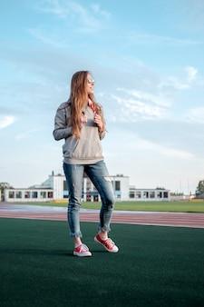 Giovane donna di stile hippie bianco rossa con bandana bandiera americana, legata sul collo, godendo della luce solare sullo stadio atletico.