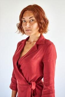 Donna rossa che guarda con fiducia la fotocamera, signora seria con i capelli corti e le lentiggini carine in posa