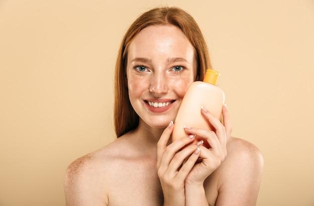 Redhead woman holding crema per la cura della pelle.