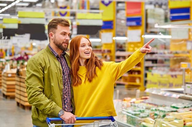 Donna rossa mostra qualcosa al marito, nel supermercato. giovane coppia sposata in abbigliamento casual nel negozio di alimentari