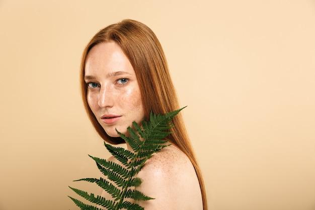 Redhead donna in piedi isolato sul muro beige azienda foglia fiore pianta.