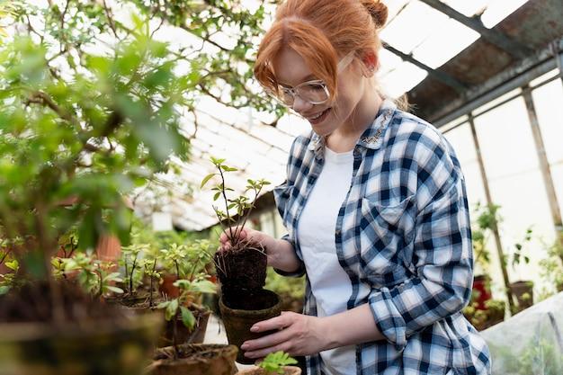 Donna dai capelli rossi che si prende cura delle sue piante in una serra Foto Premium