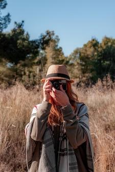 Donna rossa che scatta foto all'aperto