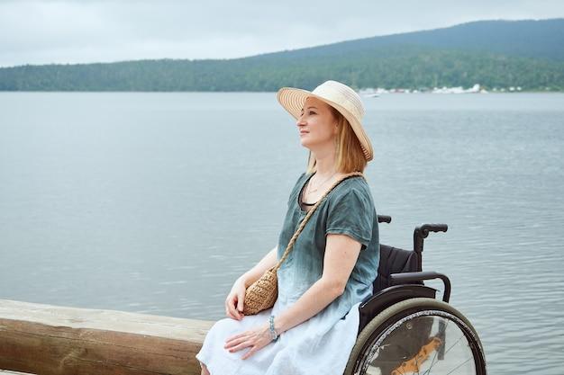 Redhead donna in sedia a rotelle con cappello godendo di vista sul mare o sul lago.
